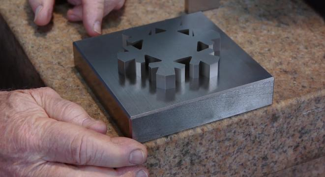 Metal Snowflake Looks Like It's Melting Into A Steel Block