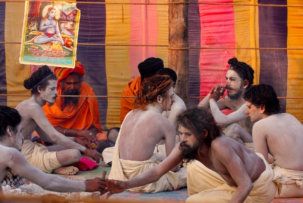 Image: Newly initiated 'Naga Sadhus' sit after performing evening rituals at the Akhara camp during the Maha Kumbh festival in Allahabad on January 29, 2013.