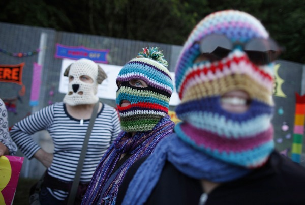 Image: Protesters wearing knitted balaclavas protest at the fence near the G8 Summit at Lough Erne Resort in Enniskillenin Northern Ireland.