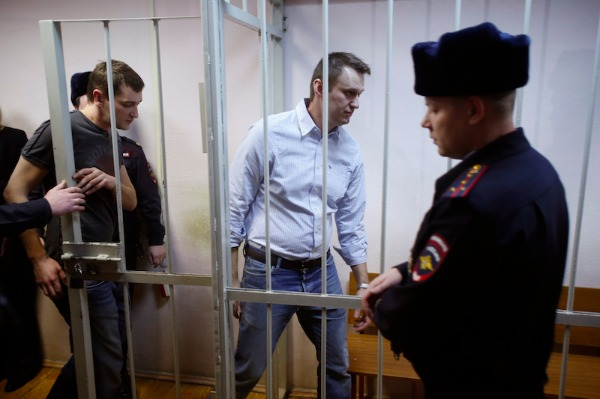 Image: Russian opposition activist and anti-corruption crusader Alexei Navalny, 38, second right, and his brother Oleg Navalny, left, enter into the cage at a court in Moscow, Russia, Tuesday, Dec. 30, 2014. Alexei Navalny, the anti-corruption campaigner who is a leading foe of Russian President Vladimir Putin, has been found guilty of fraud and given a suspended sentence of three and a half years.