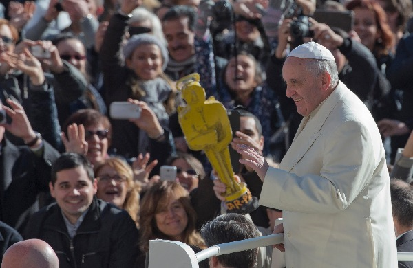 Image: A person holds a mock Oscar statue as Pope Francis tours St. Peter's Square at the Vatican prior to the start of his weekly general audience, Wednesday, March 5, 2014.
