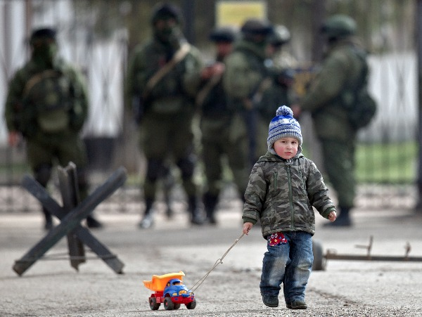 Image: A child drags a toy truck past pro-Russian soldiers standing outside an Ukrainian military base in Perevalne, Crimea. With thousands of Ukrainian soldiers and sailors trapped on military bases, surrounded by heavily armed Russian forces and pro-Russia militia, the Kiev government said it was drawing up plans to evacuate its outnumbered troops from Crimea.