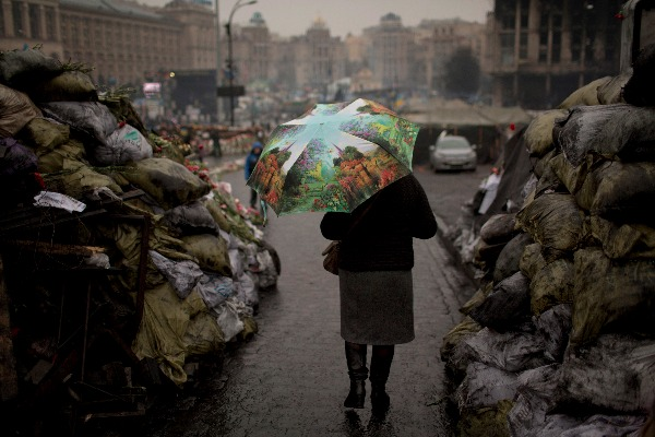 Image: A woman walks past barricades set up by anti-Yanukovich protestors at Kiev's Independence Square, in Ukraine.