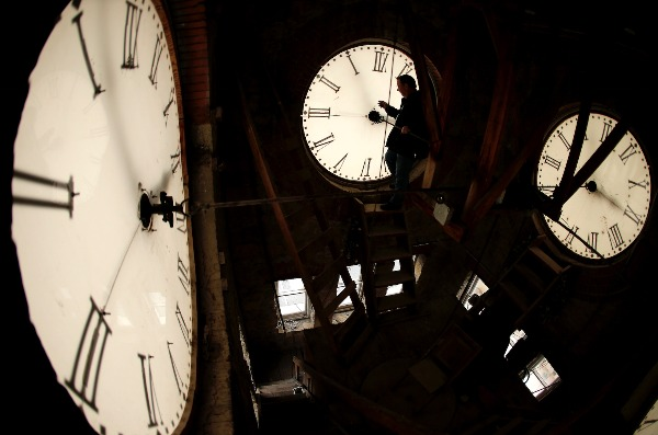Image: Custodian Ray Keen inspects a clock face before changing the time on the 100-year-old clock atop the Clay County Courthouse Saturday, March 8, 2014, in Clay Center, Kan.