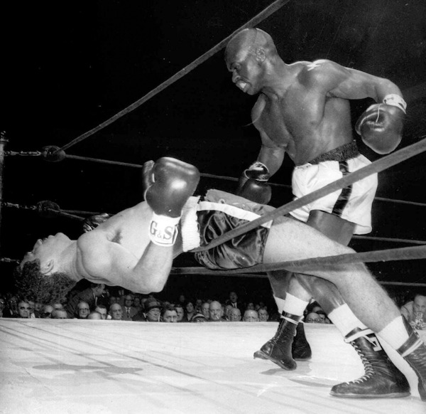 Image: Rubin Carter watches Cuba's Florentino Fernandez fall through the ropes as he was knocked out in the first round of their scheduled 10-round bout at Madison Square Gardens, New York, on Nov. 3, 1962. Carter passed away Sunday at the age of 76.