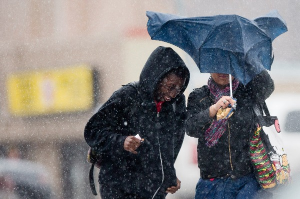 Image: Pedestrians walk with little protection from their collapsed umbrella during a rainstorm, Wednesday, April 30, 2014, in Philadelphia. The area can expect widespread showers with possible thunderstorms with a flood watch in effect through Thursday morning.