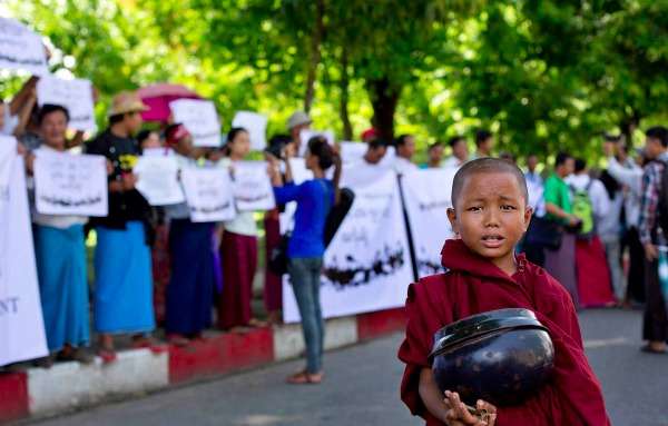 Image: A novice Buddhist monk stands in front of a group of protesting people in Yangon, Myanmar, Tuesday, May 27, 2014. The small group of civil society activists staged a protest calling for an amendment to Myanmar's constitution that bans opposition leader Aung San Suu Kyia becoming the country's president.