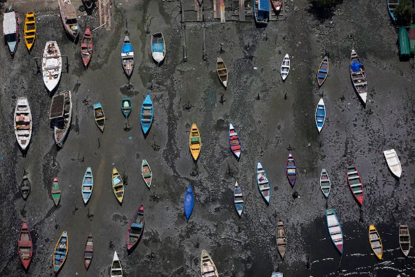 Image: Small boats sit on the shore of Guanabara Bay across the bay from Rio de Janeiro, Brazil. Rio dumps almost 70 percent of its untreated sewage into its surrounding waters, which fouls the bay with human waste and floating debris.