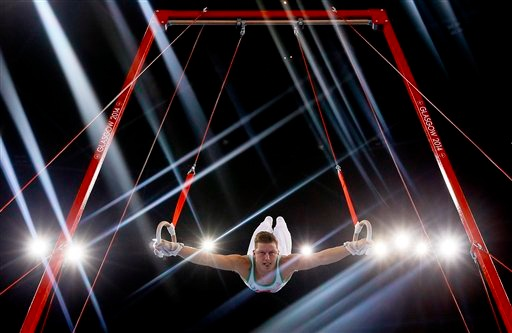 Image: Lights flare as Harry Owen of Wales performs on the rings during the Men's All-Around gymnastics competition at the Scottish Exhibition Conference Centre during the Commonwealth Games 2014 in Glasgow, Scotland.