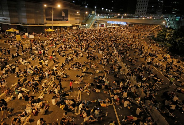 Image: Protesters take rest at a main road in the financial central district after riot police use tear gas against them as thousands of people blocked the road in Hong Kong, Sunday, Sept. 28, 2014. Hong Kong police used tear gas on Sunday and warned of further measures as they tried to clear thousands of pro-democracy protesters gathered outside government headquarters in a challenge to Beijing over its decision to restrict democratic reforms for the city.