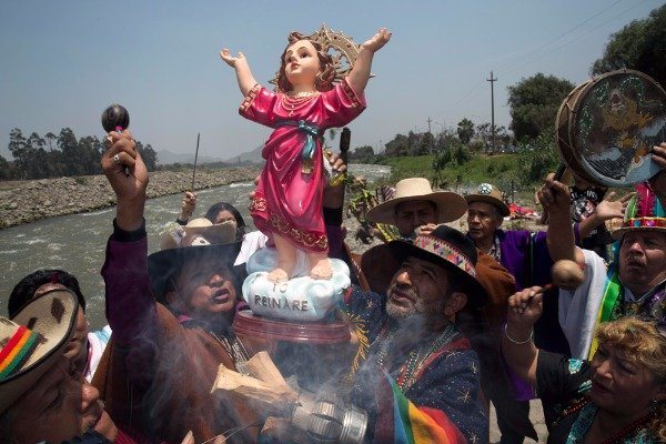 Image: ​Shamans hold up a statue of baby Jesus, or