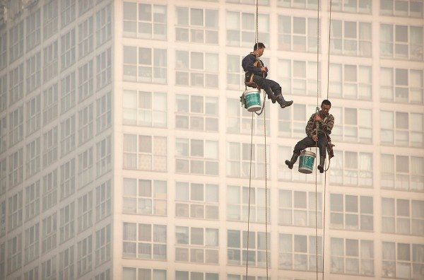 Image: Window washers use cables to lower themselves from a skyscraper while working on a polluted day in Beijing, Tuesday, Oct. 6, 2015. Air quality readings in the city on Tuesday were at levels considered hazardous by international measuring standards.​