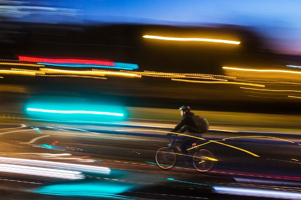 Image: A cyclist rides in between cars in Madrid, Spain, Tuesday, Feb. 24, 2015. A public bike rental scheme was inaugurated last year but there are still few cycling lanes in the Spanish capital.