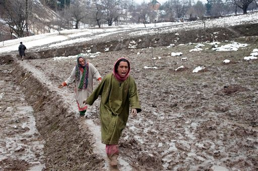 Image: Kashmiri women wail and rush towards the body of a relative, victim of a landslide, as the same is recovered in the village of Laden some 45 Kilometers (28 miles) west of Srinagar, Indian-controlled Kashmir, Monday, March 30, 2015. Hundreds of Kashmiris in both India and Pakistan moved to higher ground Monday as rain-swollen rivers swamped parts of the disputed Himalayan region placed under an emergency flood alert just six months after some 600 people died in flooding that left the region in shambles.