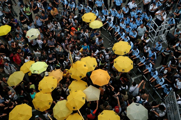 Image: Protesters holding yellow umbrellas gather to observe a moment of silence to mark the first anniversary of