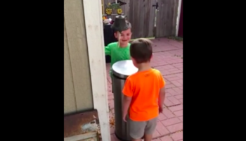 Two Kids Have A Questionably Good Time Hitting Each Other In The Face With Trash Can Lid