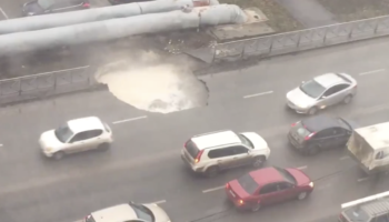 A Massive Sinkhole Opens On A Road In Russia, And Drivers Very Casually Navigate Around It