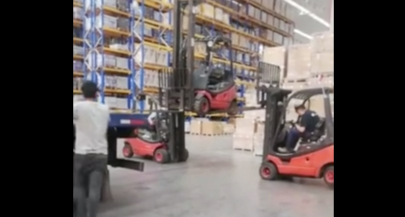 Workers Try To Use Forklifts Unload Another Forklift From A Truck, Which Is Really Dumb