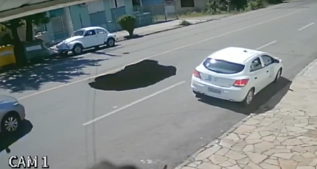 Driver Doesn't Spot Newly-Formed Sinkhole, Drives Straight Into It
