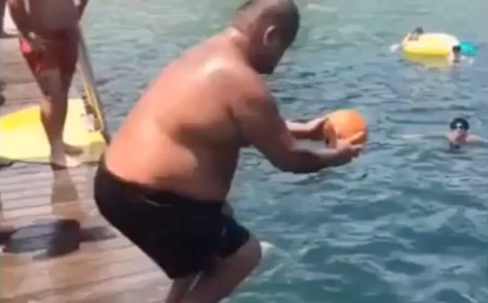 Guy Jumps Into The Water Holding A Ball, Nearly Launches It Into Orbit