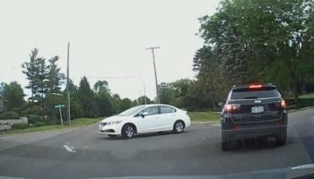This Hesitant White Sedan Demonstrates What Not To Do When Merging Into Oncoming Traffic