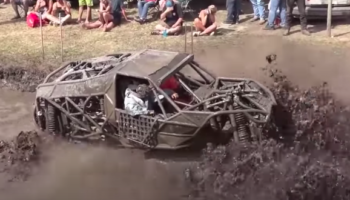 Watch Trucks Try To Climb Their Way Out Of A Giant Muddy Trench