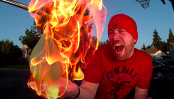 Guy Sets His Hand On Fire, Tests To See If That Will Pop A Water Balloon